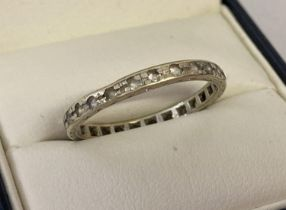 A vintage 14ct white gold full eternity ring set with clear stones. Worn mark to edge of ring. Tests