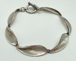 A modern design silver bracelet with leaf style links and T-bar clasp. Brushed silver detail to