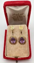 A pair of vintage decorative 14ct gold, amethyst set screw back earrings with floral decoration