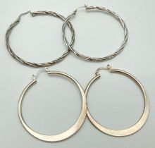 2 pairs of large silver hoop earrings. A pair of plain hoops together with a pair of twist design