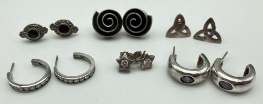 6 pairs of silver and white metal half hoop and stud style earrings. To include purple stone set