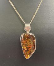A modern design silver and amber pendant on a 18 inch curb chain with spring clasp. Pendant bale and