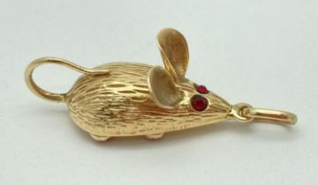 A 14ct gold mouse shaped charm/pendant set with 2 small garnets for eyes & 4 small round coral