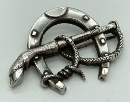 A vintage white metal horseshoe shaped brooch with rope and deer's hoof detail. Brooch clasp is