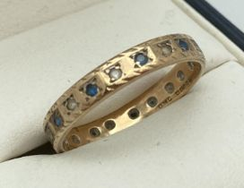 A vintage 9ct gold full eternity ring set with blue and clear stones (one missing). Full hallmarks
