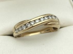 A 9ct gold, ¼ct diamond dress ring in crossover design set with 11 small round cut diamonds. Full