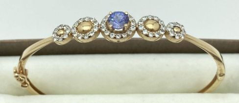 A 14ct gold hinged bangle with stone set flower design to top. Central oval iolite stone