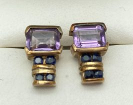 A pair of 9ct gold, amethyst and sapphire stud style earrings. Each earring set with a square cut