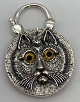 A double sided silver pendant with opening bale. Carved cats face detail to one side and round