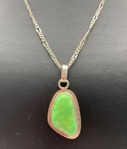 A modern design green stone set pendant on a 22 inch silver Figaro style chain with spring clasp.