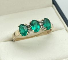 A 9ct gold diamond and created emerald dress ring. 3 oval cut emeralds in a trilogy setting, with