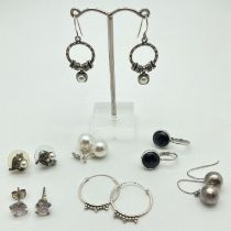 7 pairs of silver and white metal drop and stud style earrings. To include decorative hoops, faux