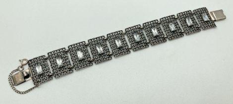 A vintage style silver bracelet with 10 lattice style square links each set with a baguette cut