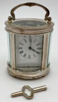 A small oval shaped carriage clock with glass panelled sides and top, enamelled face and roman