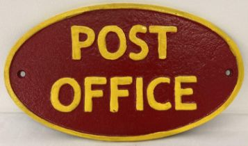 A painted cast iron oval shaped Post Office wall plaque. In red and yellow and with fixing holes.