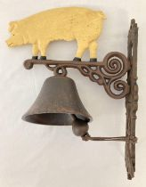 A painted cast metal wall hanging garden bell with pig design. Approx. 34cm x 28cm.