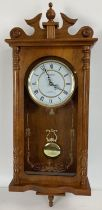 A modern wooden cased wall hanging Acctim quartz Westminster chime clock. With glass front panel,