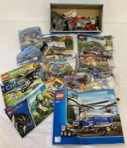 A collection of assorted Lego play pieces and instruction manuals.