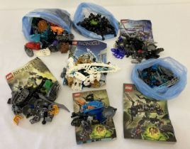 A collection of assorted Lego Bionicle play pieces and instructions.