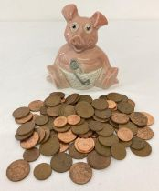 """A ceramic """"Woody"""" baby pig money box by Wade containing a quantity of British 2 and 1 pence coins…"""