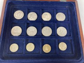 A wooden coin display box with blue baize lined interior & contents. Contents comprise 8 x commem…