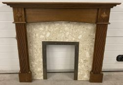 A cream marble and brass fire surround with carved wooden mantle. Column detail and carved floral
