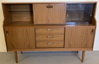 A vintage mid century Schreiber teak sideboard with sliding doors, drawers and glass shelves.