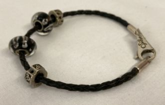 A silver and black plaited leather bracelet by Silverado, together with 4 charm beads.