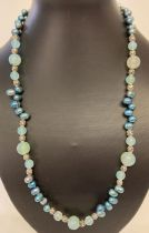 """A 22"""" peacock blue freshwater pearl and aquamarine beaded necklace with white metal spacer beads."""