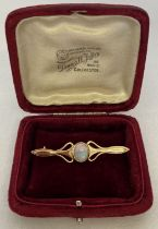 A gold Art Nouveau style bar brooch set with a central opal, tests as 9ct gold.