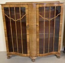 A walnut veneer, serpentine fronted Art Deco 2 door glass cabinet.