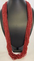 A multi strand coral chip necklace with silver tone hook and eye claps.