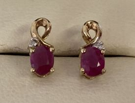 A pair of 9ct gold ruby and diamond stud style earrings with gold twist design.