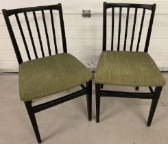 A pair of retro black wooden stick back style kitchen/dining chairs with green upholstery seats.