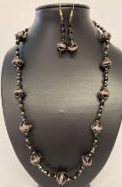 A matching necklace and earrings set made with black Venetian style glass beads.