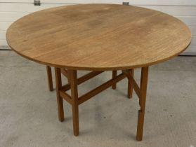 A vintage 1970's teak circular drop leaf, gate leg table.