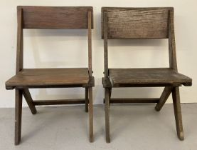 A pair of dark oak Arts & Crafts folding chairs with solid wood seats and x shaped frame.