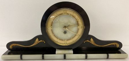 An Art Deco black slate and onyx mantle clock with gold scroll applique detail.