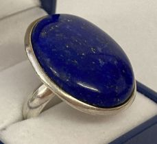 A modern silver statement dress ring set with a large oval lapis lazuli stone.