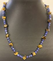A lapis lazuli and square shaped tigers eye beaded necklace with flower shaped T bar clasp.