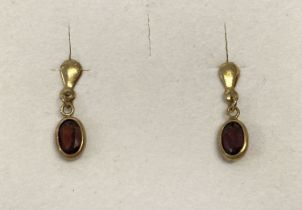 A small pair of 9ct gold and garnet set drop style earrings.