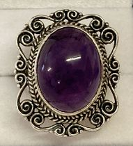 A large statement silver dress ring set with an oval amethyst cabochon stone.
