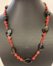 """A 19"""" costume jewellery necklace made from disc shaped coral beads and polished onyx beads."""