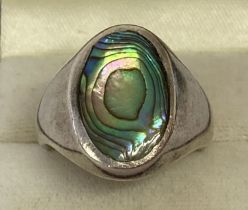 A men's silver signet ring set with an oval of paua shell. Marked 925 to inside of band.