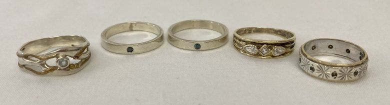5 silver and white metal stone set band style rings in varying sizes and designs.