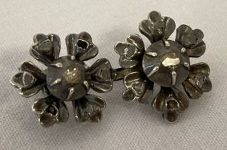 A vintage double flower design white gold brooch set with diamond chips.
