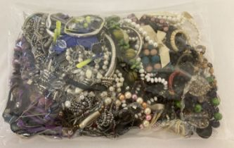 A sealed bag of mixed modern costume jewellery to include faux pearl bracelets and beaded necklaces.