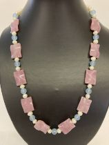 """A 22"""" fresh water pearl necklace with pink and square shaped blue jade beads & gold tone hook clasp."""