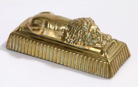 Brass sleeping lion door stop, on a weighted gadrooned plinth base, 22cm wide, 9cm high