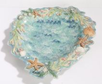 Pottery dish with starfish, shell and seaweed decorated border, initialled AW to base, 35cm wide